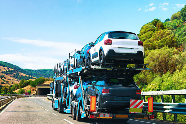 The cost to ship a car can be effect by the origin and destination. Image is of multiple cars being hauled on a trailer.